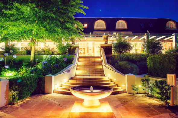 Exterior of the Le Franschhoek Hotel and Spa at night.